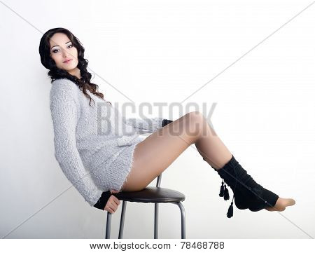 Female model in cardigan on a chair