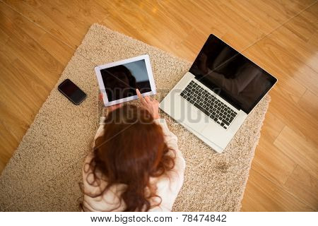 Pretty woman lying on floor using technology at Chritmas at home in the living room