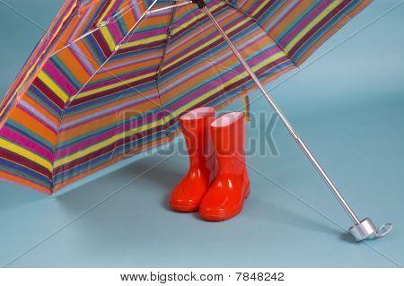 Red Children Rain Boots And A Colorful Umbrella