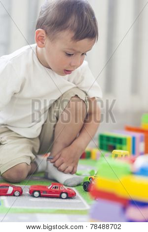 Portrait of Little Caucasian Boy Playing with Toys Indoors. Verticl Image Composition poster