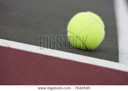 Tennis balls sitting on the ground at a tennis court poster