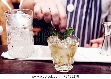 Bartender is making cocktail at bar counter, toned