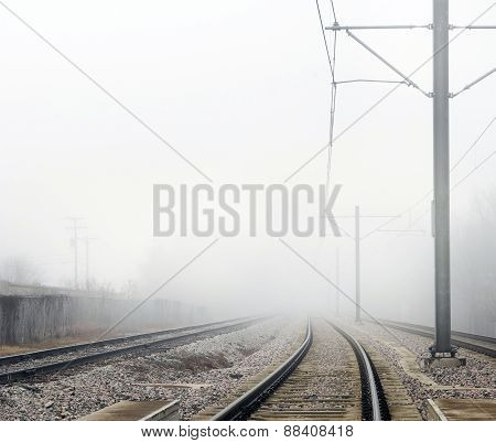 Railroad Track Disappearing Into Fog Horizontal