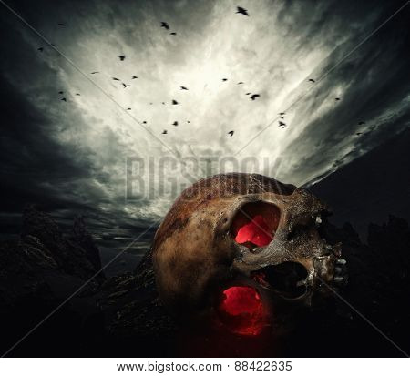 Human skull with glowing eyes against stormy sky