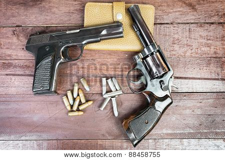 Black Revolver Gun And Semi-automatic 9Mm Gun On Wooden Background
