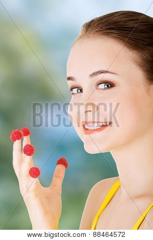 Cacuasian woman with raspberries on fingers.