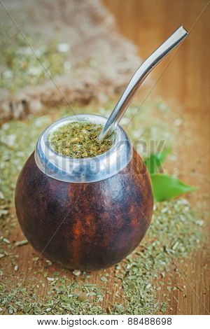 Latin traditional yerba mate tea in calabash with bombilla on wooden table