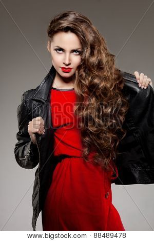 Beautiful young woman model brunette with long curled hair with red lips in leather jacket. Girl wave, curly hairstyle. Health hair shine. Beauty lady face with sexy glance.