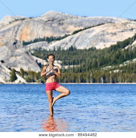 Yoga woman meditating in nature meditation retreat. Young female adult relaxing standing in tree pose in the middle of a serene lake surrounded by mountains and forest for a relaxation concept.
