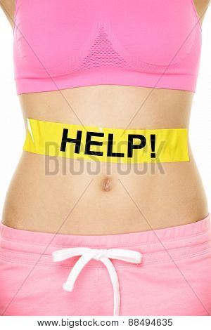 Stomach help concept - woman with body weight problem. Closeup of waist of female adult showing yellow label on abdomen with word HELP written for digestion, health, reproduction or diet issues.