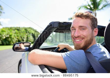 Driving car man happy on road trip travel holidays. Portrait of a young adult smiling at camera ready for his vacations with his new convertible purchase or leasing.
