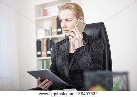 Pensive Manageress With Tablet Calling On Phone