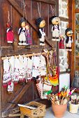 Variety of traditional bulgarian souvenirs textile, spoons and dolls on the wooden door poster