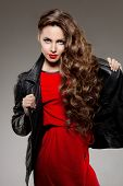 Beautiful young woman model brunette with long curled hair with red lips in leather jacket. Girl wave, curly hairstyle. Health hair shine. Beauty lady face with sexy glance. poster