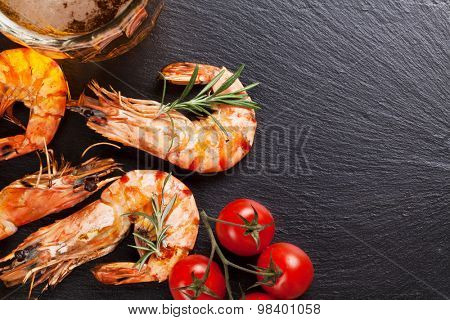 Beer mug and grilled shrimps on stone plate. Top view with copy space