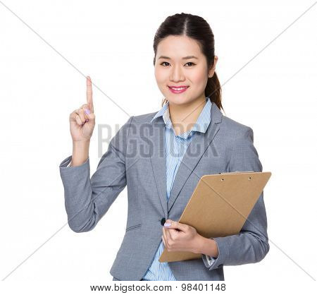 Asian young businesswoman carry with clipbaord and finger point up
