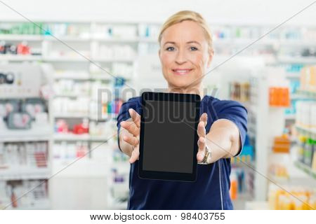 Portrait of mature female pharmacist showing digital tablet with blank screen in pharmacy