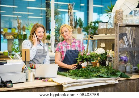 Florist using mobile phone while colleague making bouquet at counter in flower shop