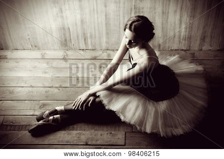 Professional ballet dancer resting after the performance. Art concept. Black-and-white photo.