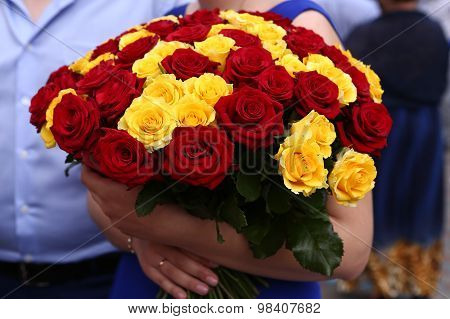 red and yellow roses bouquet in the hands