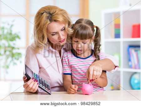 family - middle aged woman and her daughter with pink piggy bank and calculator