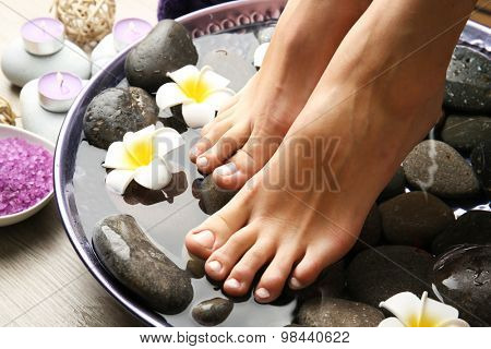 Female feet at spa pedicure procedure poster