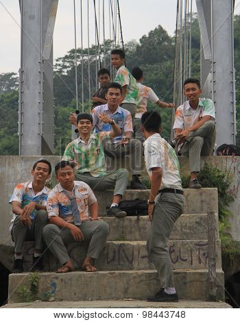 schoolboys are sitting on steps nearly the bridge in Bukit Lawang, Indonesia