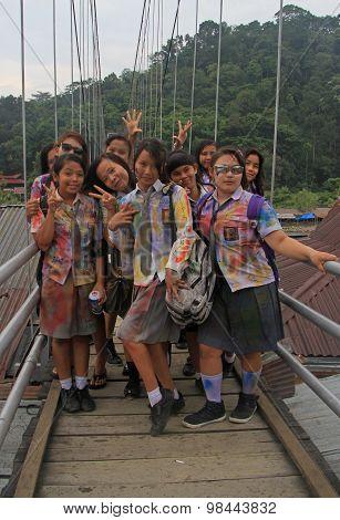 schoolgirls are smiling on the bridge in small village Bukit Lawang