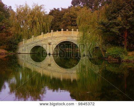 Bridge, water, trees, reflection in Hangzhou China