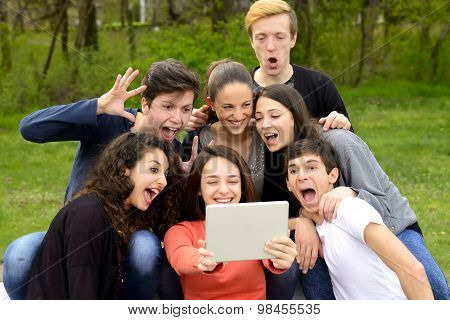 Group of friends having fun and goofing around while using a tablet in a park