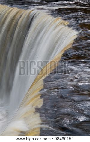 Tannin-stained whitewater pours over the brink of Upper Peninsula Michigan's Tahquamenon Falls the second largest waterfall east of the Mississippi. poster
