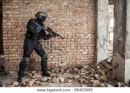 Special forces operator in black uniform and bulletproof poster