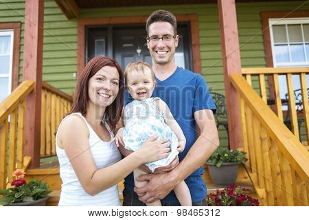 Portrait of couple with their adorable daughter in front of hous