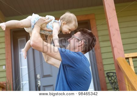 father and daughter play in front of the house
