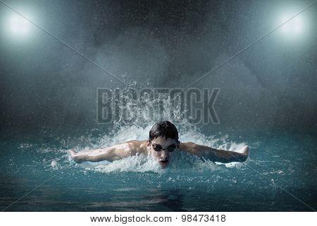 Swimmer in waterpool, butterfly style