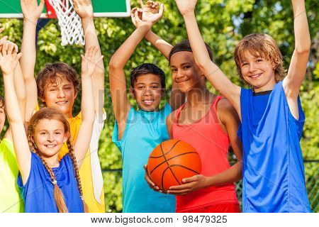 Friends hold arms up at basketball game