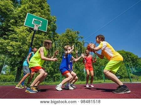 Teenage children playing basketball game together