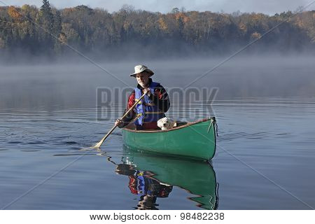 Man Paddling A Canoe With A Small White Dog In The Bow