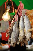 Dried salted fish hanging in the market poster