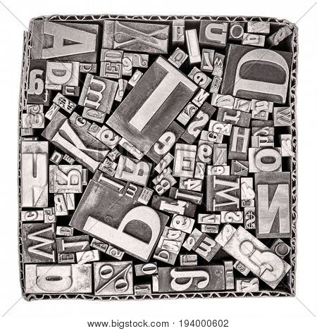 vintage letterpress metal type printing blocks in a cardboard box isolated on white, black and white image