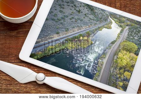 Rodeo Rapid on the upper Colorado River at Burns, Colorado, USA, - reviewing and editing aerial image on a digital tablet