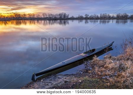 a slim sea racing kayak ready for paddling workout before sunrise on a calm lake in Colorado