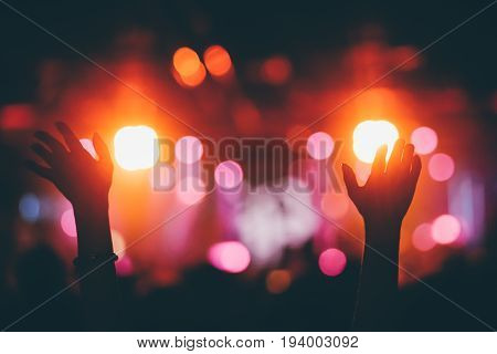 Hands raised up on a night club concert with the colorful stage lights bokeh background