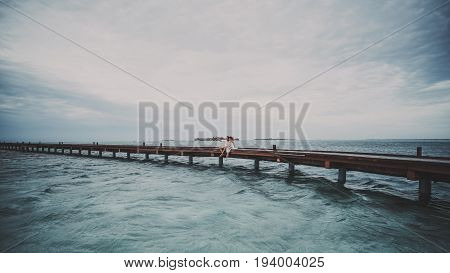 Adult caucasian couple man and woman are making selfie using modern smartphone on Maldives resort while sitting in the centre of bridge on warm windy weather with overcast sky and waves on ocean water
