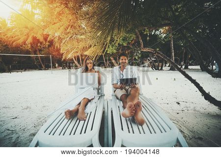 Two beautiful adult people on resort beach chairs: smiling handsome man watching movie via digital tablet and charming woman working on her modern laptop during their vocation on warm sunny evening