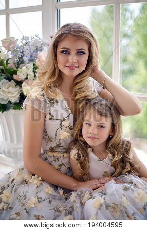 mother and daughter sitting in the studio neareby large window in matching dresses with flowers