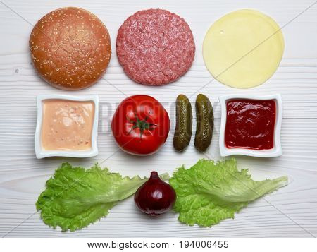 Ingredients for hamburger on white wooden table.