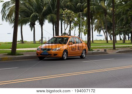 Sanya Hainan China April 24 2017 - Kia Cerato car taxi service stands on the roadside along the asphalt road along the coastline
