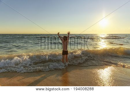 kid delighted by the sea. boy on the beach looking at ocean waves at sunset. hands raised up