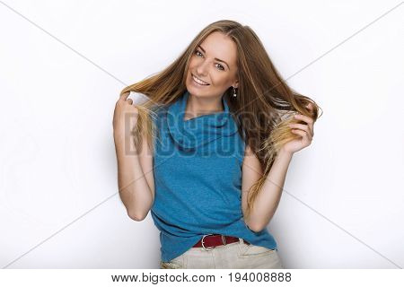 Headshot Of Young Adorable Playful Blonde Woman With Cute Smile In Cobalt Color Blouse Posing On Whi